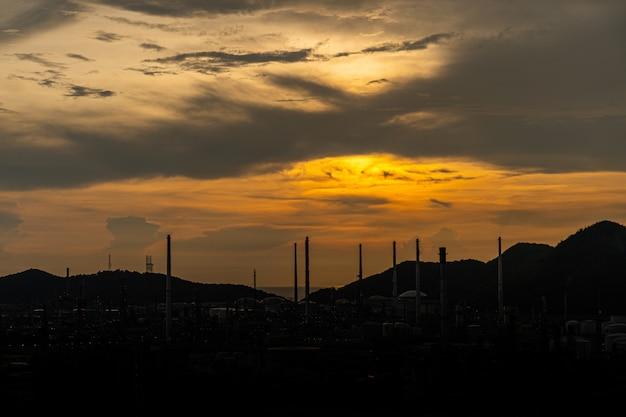 Нефть или газ нпз на закате. силуэт нефтяного или газового промышленного завода на закате с красочным небом позади
