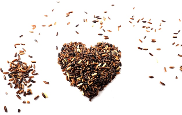 赤い生米、玄米、混合穀物をハート型、健康的なコンセプト、バレンタインコンク