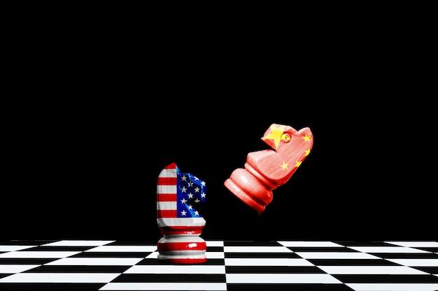 アメリカと中国の旗は黒の馬のチェスにスクリーンを印刷します。