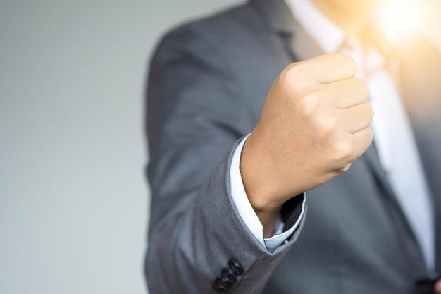 エグゼクティブビジネスマンが戦いのための心を加速するために拳の手を上げる