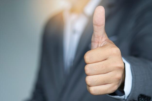 Бизнесмен показывает сигнал с поднятым вверх большим пальцем