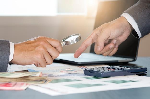 Бизнесмен держит стекло лупы для анализа финансовых данных