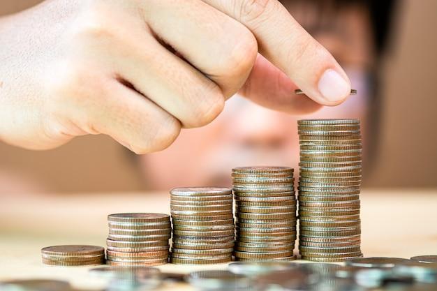 Рука положить монеты укладки для сохранения в будущем и фонд фондовых инвестиций.