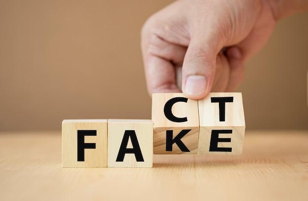 Рука подбрасывает деревянные кубики для изменения формулировки от факта к подделке
