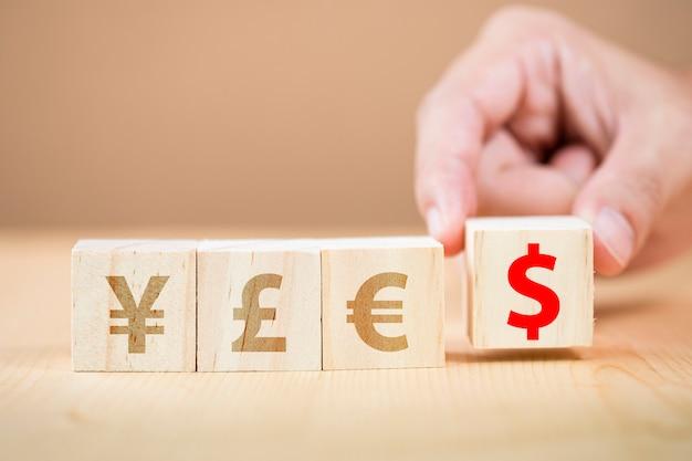 木製の立方体米ドル記号を元円ユーロポンドに入れてサインを手します。米ドルは世界の主要な交換通貨です。
