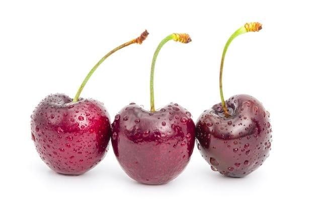Свежая изолированная красная вишня с капелькой