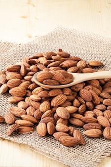 クローズアップアーモンドナッツは、袋とテーブルに木のスプーンから注がれています。