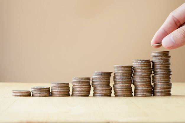 Укомплектуйте личным составом руку кладя монетки штабелируя для дела роста и концепции вклада сбережений.