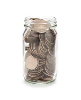 白い背景の上のガラスの瓶にコインがいっぱいのクローズアップ。クリッピングパスの写真と投資の概念を保存すると分離されました。