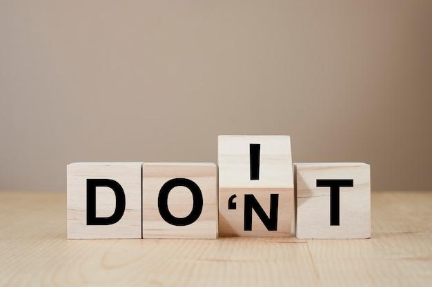 Рука переворачивает деревянные кубики для смены «не надо» на «делай это». уверенная концепция.