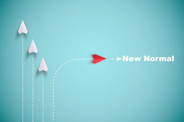 赤い紙飛行機が白い紙と一線を外して、青い背景に混乱を起こし、新しい通常の方法を見つけます。革新技術を発見するためのリフトとビジネス創造性の新しいアイデア。
