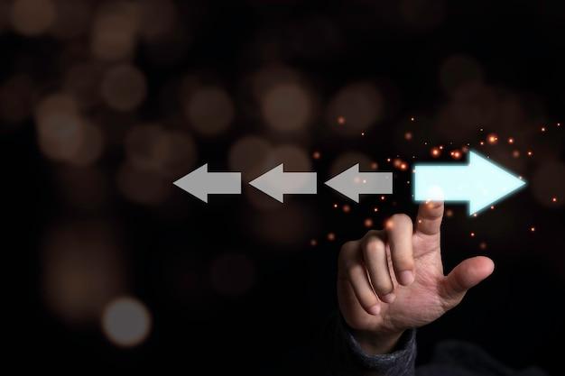 白い矢印と反対方向の水色の矢印に触れる手。新しいテクノロジーと新しいビジネスチャンスの概念を発見するための混乱と異なる考え方。