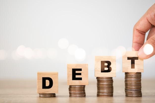 コインスタッキングで木製の立方体に画面を印刷する借金文言を置く手。債務増加の概念。