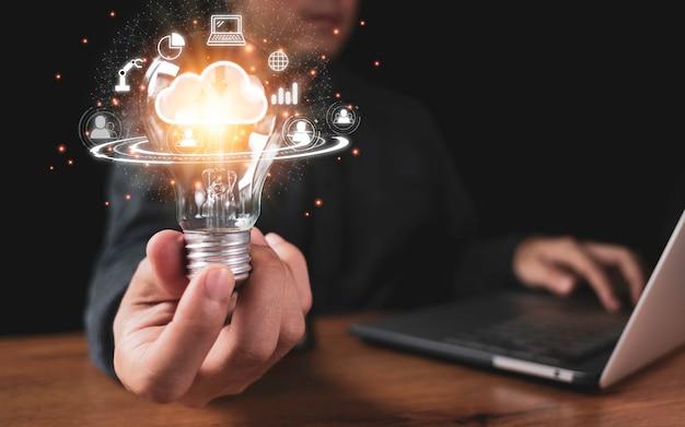 ラップトップコンピューターのグラフなどのクラウドコンピューティングとテクノロジーのアイコンと電球を持っている手。クラウドテクノロジー管理のビッグデータにはビジネス戦略が含まれます