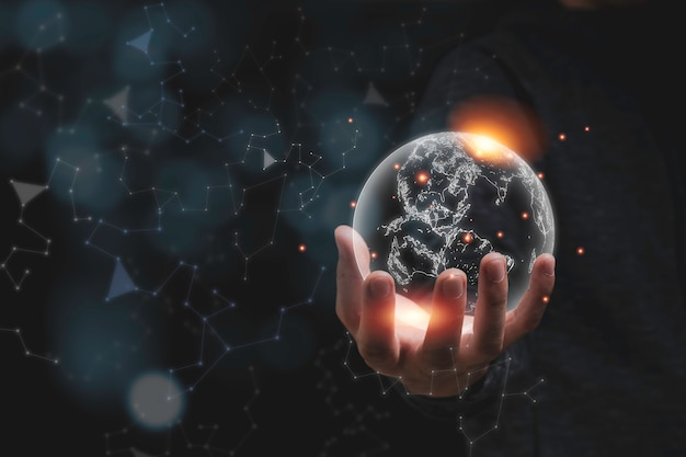 オレンジ色の光で仮想世界を持っている手。環境保全の概念。