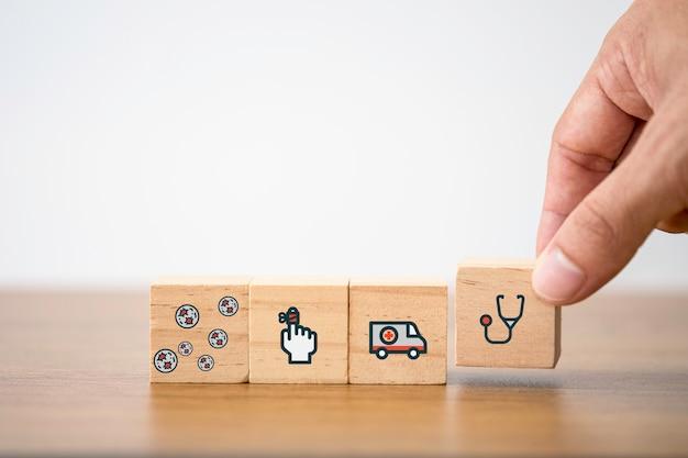 テーブルに医療医学と病院のアイコンの木製キューブを置く手。医療保険事業および投資。