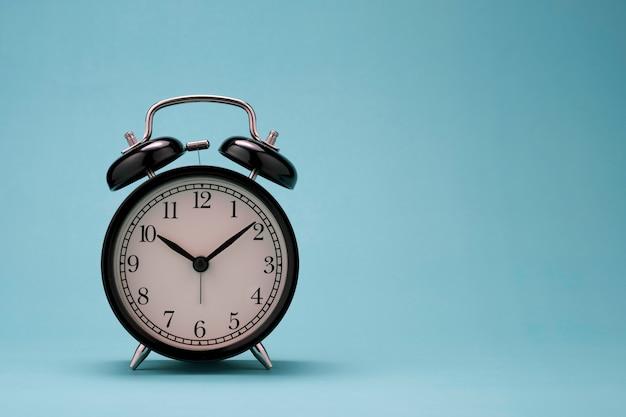 緑の背景に美しい黒い目覚まし時計のクローズアップ