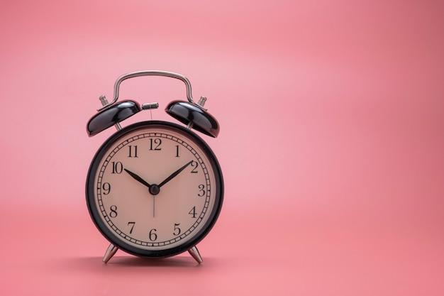 ピンクの背景に美しい黒い目覚まし時計のクローズアップ