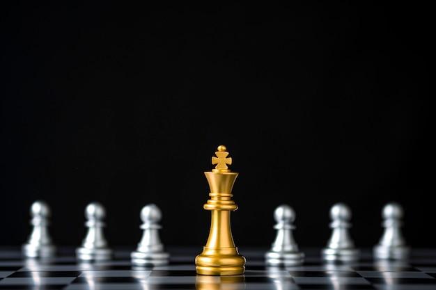 Золотой шахмат короля перед серебряными шахматами пешки на шахматной доске и черной предпосылке.