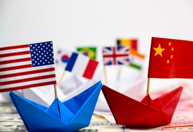 青い船と中国の旗の上にアメリカの国旗、戦争のトラートの白い背景と赤い船に