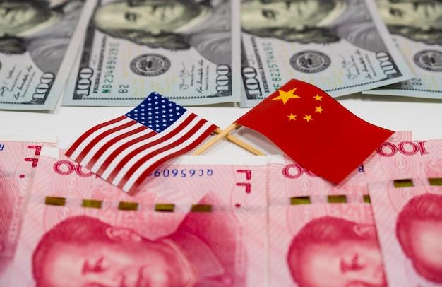 アメリカの旗と中国の旗の向こう側にある米ドルの紙幣と中国元の紙幣