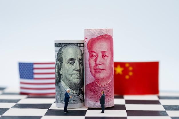 チェスのテーブルの上のフラグとアメリカドルと中国人民元の紙幣。それは関税貿易戦争危機の象徴です