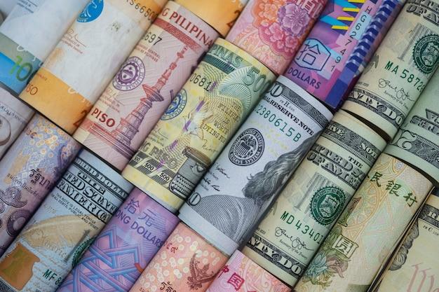 クローズアップは、世界中のさまざまな紙幣を巻きました。為替レートと外国為替投資の概念