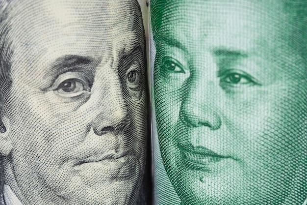 Крупным планом лицом к лицу бенджамина франклина и мао цзэдуна от банкнот доллара сша и китайских юаней.