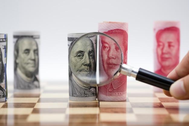 チェス盤の上の拡大鏡ガラスと米ドルと人民元の紙幣