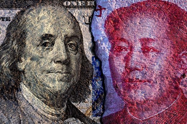 Треснувший лицом к лицу банкноты доллара сша и китайской банкноты юаня