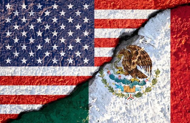アメリカの国旗とひびの入った壁にメキシコの国旗