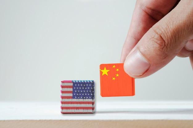 印刷画面中国国旗とアメリカ国旗の木の立方体を置く手。それはアメリカ合衆国と中国の間の関税貿易戦争税の障壁の象徴です。