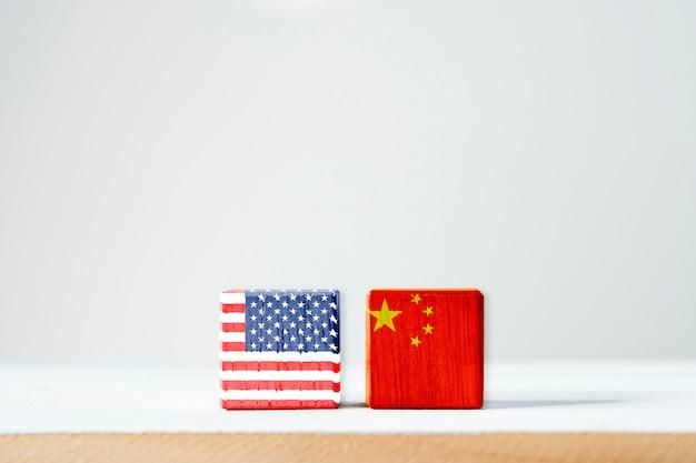 アメリカの国旗と中国の国旗が木製の立方体の画面を印刷します。それはアメリカ合衆国と中国の間の関税貿易戦争の税の障壁の象徴です。