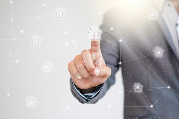 土地所有権と不動産開発を拡大するためのホームアイコンネットワークに触れるビジネスマネージャー