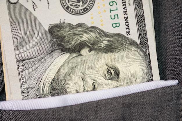 灰色のスーツのポケットに米ドル紙幣のクローズアップ。投資と支払いの概念。