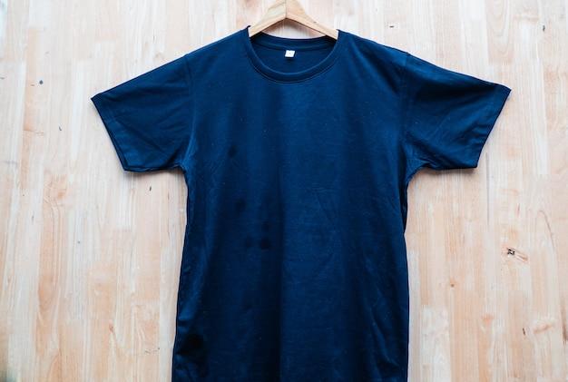 Черная футболка с коротким рукавом однотонная круглая шея макет концепция идея деревянный задний фон вид спереди