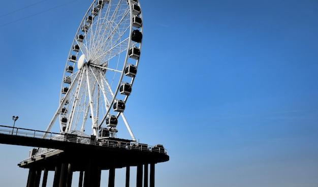 Колесо обозрения на фоне голубого неба летом
