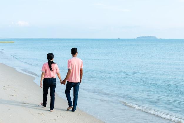 夏休みにビーチを歩くカップル