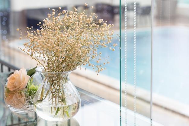 プールのそばのガラスの横に置かれた花瓶の花