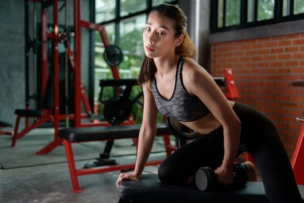 フィットネス女性、スポーティーな女性、ダンベルと筋肉をポンピングするアジアの運動女性。