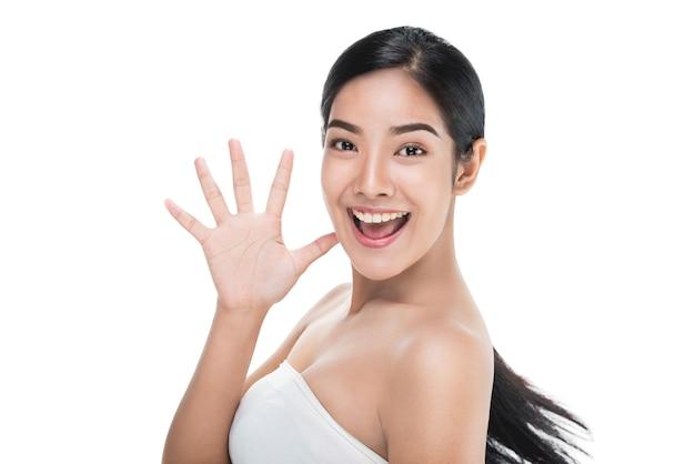 Красивая женщина заботится о лицо кожи, показывая знак привет