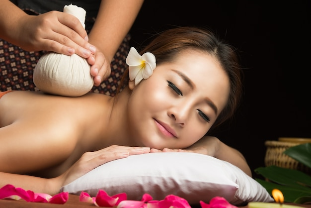 Азиатская женщина получает массаж травяной травяной массаж в спа