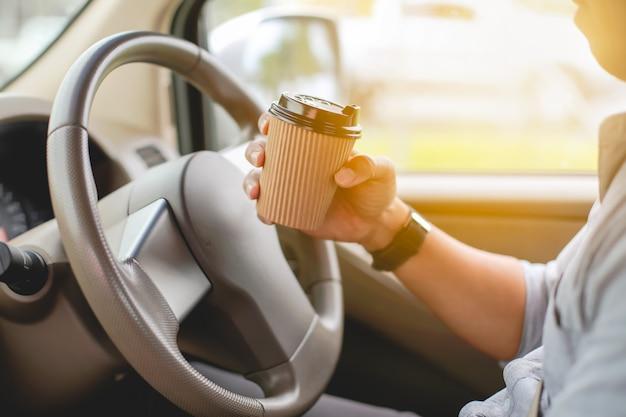 運転手が車の中でコーヒーを飲みます。
