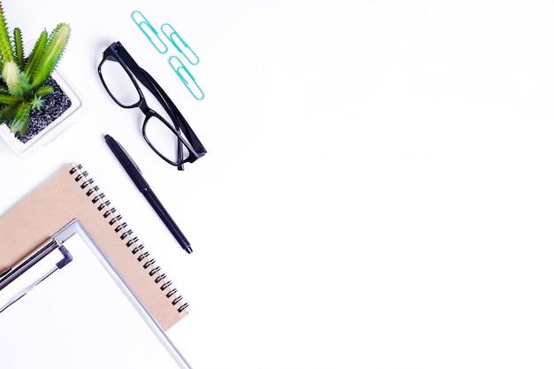 メガネの短いメモ用紙、オフィスの植物、ペンとクリップのオフィスデスクテーブル。