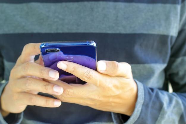 ソーシャルネットワークに接続するためにスマートフォンを使用している男性。