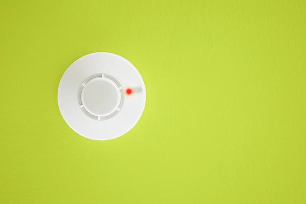 黄色の背景に煙探知器。セキュリティシステム。