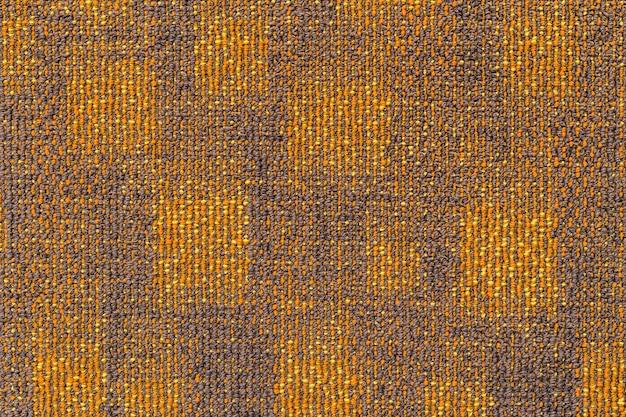 灰色がかったオレンジのカーペットの表面。