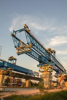 橋の建設現場の建設用クレーンと桁。新しい高速道路の建設現場と設備。
