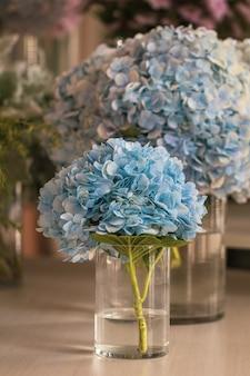 木製のテーブルの上の美しい青いアジサイの花と花瓶。青いアジサイの花を間近ぼやけて。
