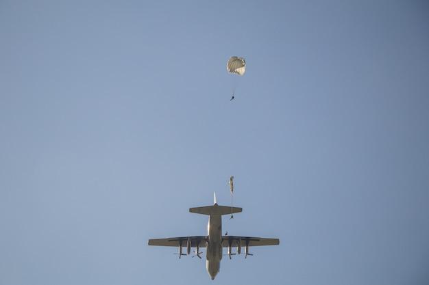 白いパラシュート、空の軍事パラシュートジャンパーで落下傘兵のジャンプ。